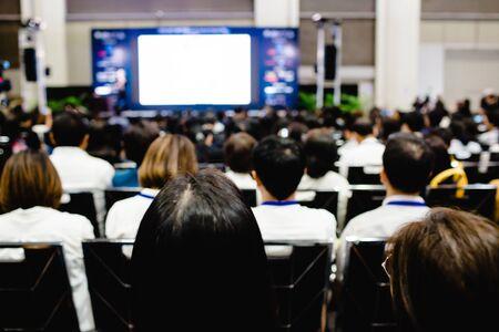 Borroso de auditorio para reunión de accionistas o evento de seminario con proyector y pantalla blanca, mucha gente de negocios escuchando en la conferencia. fondo borroso de muchas personas.