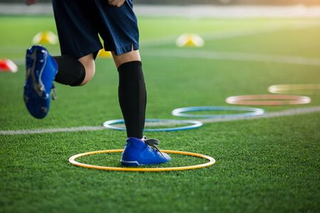 selective focus to kid soccer player Jogging and jump at ring ladder marker on green artificial turf. equipment for training class of football academy.