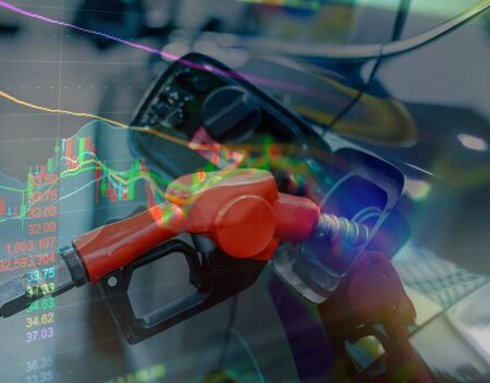 Close up of fuel monitoring system refueling a petroleum to vehicle and graph chart with the indicator on the oil price slide at gas station. Concept fluctuations in oil prices and exchange trade.