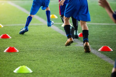 kid soccer players Jogging and jump between cone markers on green artificial turf for soccer training. football or soccer academy.