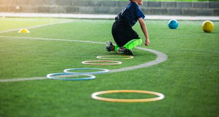 selective focus to kid soccer player Jogging and jump at ring ladder marker on green artificial turf. equipment for training class of football academy. kid football player falling while practicing.