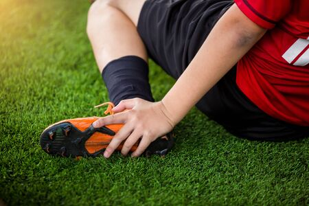 footballer is sitting and catch the ankle of the feet because of pain, soccer player was injured in the foot with pain during competition or practice.