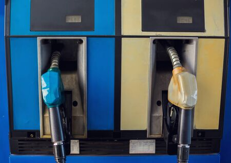 Close up blue and yellow fuel nozzles at gas station