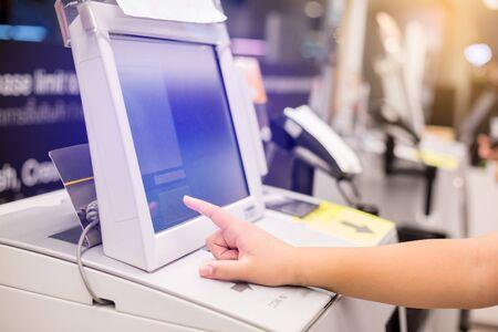 La main de l'enfant appuie sur l'écran de la machine de paiement automatique. machine en libre-service dans un supermarché moderne, caisses en libre-service, caisse libre-service dans un hypermarché. Banque d'images