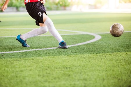 Soccer player speed run on green artificial turf to shoot ball to goal. Boy soccer player is training. Asian boy player is in football academy.