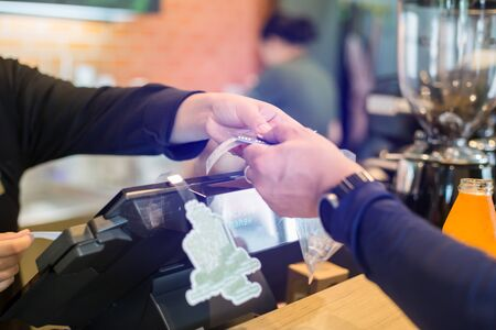 Cashier take banknote from consumer hand. Hand Paying Money To Worker In Coffee shop. Saleswoman receiving payment from male customer in store. Stock fotó