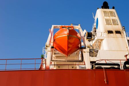 Orange lifeboat at tail of international cargo ship in the ocean for emergency evacuation loading for safety, Freight transportation, Shipping, Nautical Vessel. Reklamní fotografie