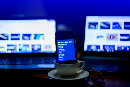 BANGKOK, THAILAND, JULY 10, 2019 : Smart phone display Facebook Libra text and it is in coffee cup with blurry laptop show business news, The concept of business news in morning, Bangkok, Thailand. Editöryel