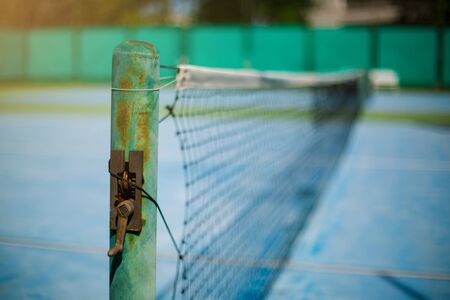 Selective focus to old tennis net with blurry green background. Tennis game. Sport, recreation concept.