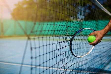 Selective focus to net with blurry tennis ball in hand and racket in court under sunlight. Tennis game. Sport, recreation concept Imagens