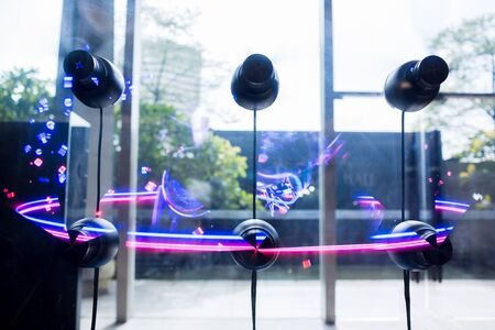 Selective focus to 3D holographic fan advertising machine on glass wall. Revolutionary media solution for creating, managing and displaying 3D video content with holographic effect. Imagens