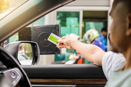Selective focus to driver hold card to scan at card reader station for open the car park door. Driver stop car and use key card to open the door for safety. security system for parking. The security concept.