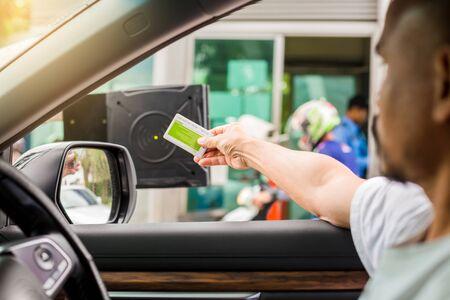 Selektiver Fokus auf Fahrerkarte, um an der Kartenlesestation zu scannen, um die Parkhaustür zu öffnen. Fahrer stoppen Auto und verwenden Schlüsselkarte, um die Tür zur Sicherheit zu öffnen Sicherheitssystem für das Parken. Das Sicherheitskonzept.