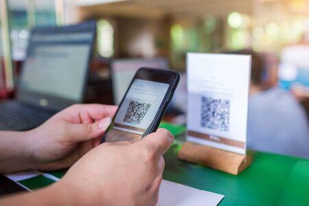 Nahaufnahme einer Hand, die Telefon hält und QR-Code mit verschwommenem Kassierer am Schalterservice scannt. Mannhände zahlen mit QR-Code. Der Kunde macht die Zahlung über Smartphone und Scan-Code. Standard-Bild