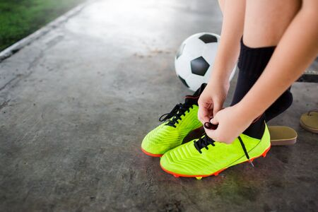 Soccer players sitting and tying Yellow sport shoelaces with soccer ball before training football or football match.