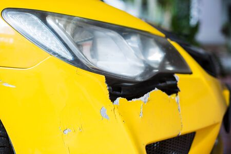 Front of yellow car get damaged by accident on the road. Yellow car crash accident, damaged automobiles after collision.