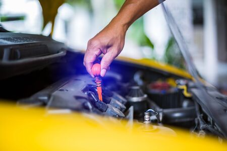 Check the oil level in yellow car engine. Mechanic checking car engine or vehicle. Check and maintenance car with yourself. Service and maintenance vehicle.