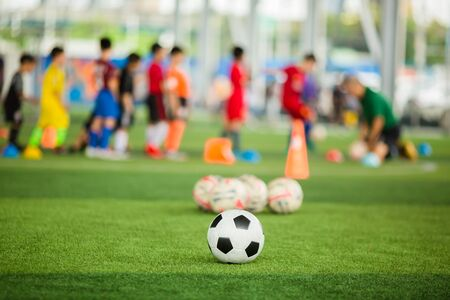 Soccer ball on green artificial turf with blurry soccer team training. Blurry kid player training and soccer equipment in soccer academy. Stock Photo
