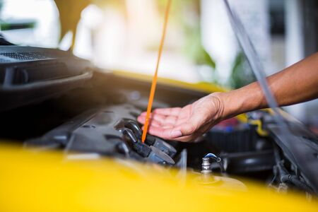 Selective focus to hand checking the oil level in car engine. Mechanic checking car engine or vehicle. Check and maintenance car with yourself. Service and maintenance vehicle.