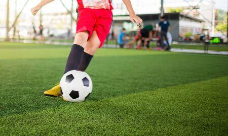 Blurry ball after boy soccer player speed run on green artificial turf to shoot it to goal. boy soccer player training. Asian player in football academy. Stock fotó