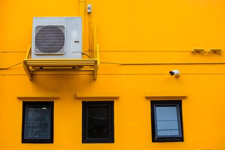 Modern air conditioner on a yellow wall. Air conditioning compressor with black glass windows on the yellow wall building background.