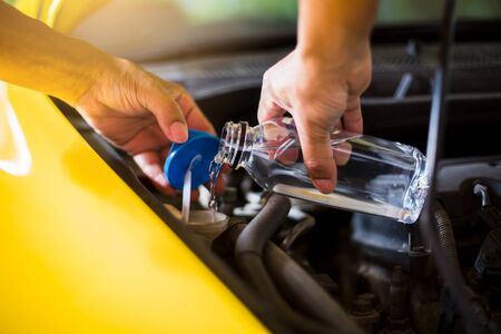 Mechanic fill fresh water into windscreen or in water tank wiper on yellow car  engine room. Service and maintenance of yellow cars or vehicles. Stock fotó