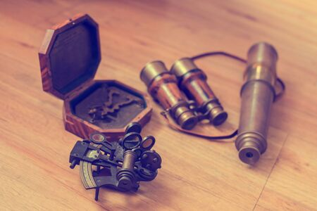 Vintage navigation equipment on wood background. Old Brass Theodolite, Wood pocket compass with cover lid, Old binoculars, old brass telescope, Traveling concept and vintage style.