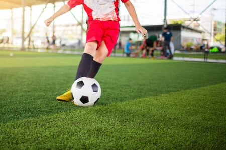 Blurry ball after boy soccer player speed run on green artificial turf to shoot it to goal. boy soccer player training. Asian player in football academy. Imagens