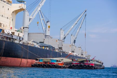 Loading goods on cargo ship with crane. Shipment from a merchant to a small ship. Grapple crane loading goods into cargo ship. Crane on cargo ship. Stock fotó
