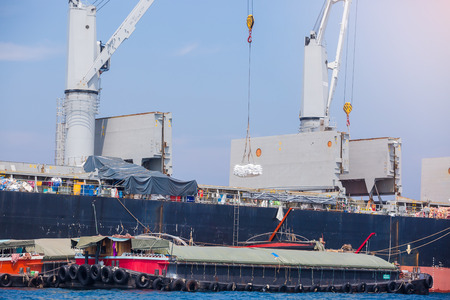 Carga de mercancías en buque de carga con grúa. Envío de un comerciante a un barco pequeño. Agarre la grúa cargando mercancías en el buque de carga. Grúa en buque de carga. Editorial