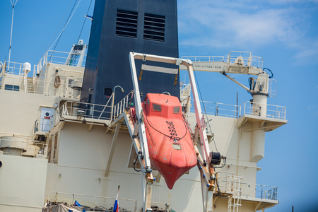 Orange lifeboat at tail of international cargo ship in the ocean for emergency evacuation loading for safety, Freight transportation, Shipping, Nautical Vessel. 新聞圖片