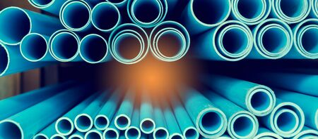 Close up to blue plastic pipe background, PVC pipes stacked in warehouse, PVC water pipes used for construction.