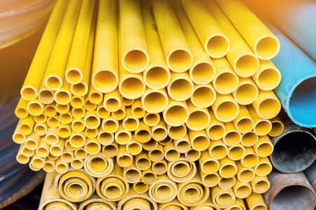 Close up to yellow plastic pipe background, PVC pipes stacked in warehouse, PVC cable pipes used for construction.