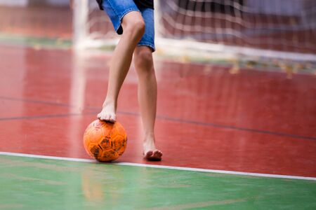 Futsal players barefoot. Futsal player control and shoot ball to goal. Indoor soccer sports hall. Football futsal player, Orange ball, Futsal floor.