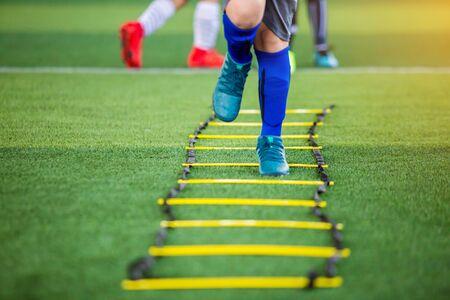 Kid soccer player Jogging and jump between marker for football training. Ladder drills exercises for football soccer team. Kid player exercises on ladder drills. Stock fotó