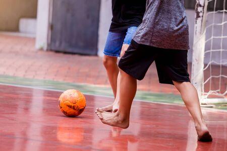 Futsal players barefoot. Futsal player  control and shoot ball to goal. Soccer players fighting each other by kicking the ball. Indoor soccer sports hall. Football futsal player, Orange ball.