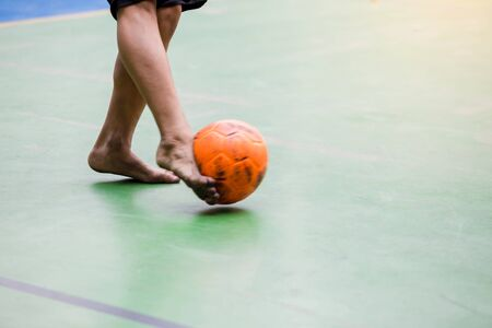 Blurry orange ball after futsal player shoot it to goal. Indoor soccer sports hall. Football futsal player, Orange ball, Red futsal floor.