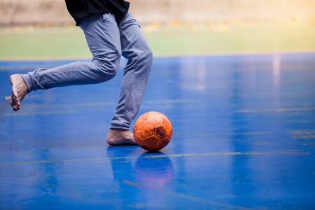 Futsal players wearing sweatpants and barefoot. Futsal player control and shoot ball to goal. Indoor soccer sports hall. Football futsal player, Orange ball, Futsal floor.