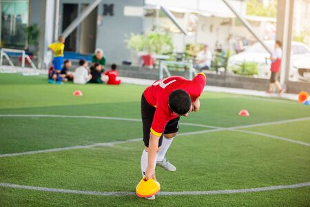 Football players are putting ring ladder marker and football training equipment on green artificial turf. Material for training class of football academy.