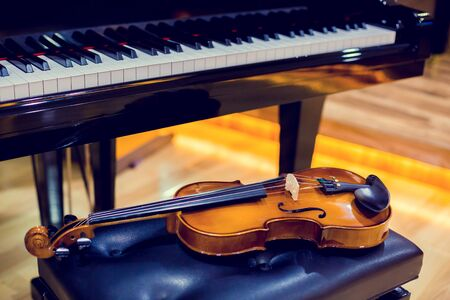 Violin and piano on wooden background. Musical instrument for learning music in music room. The music learning concept. Stock fotó