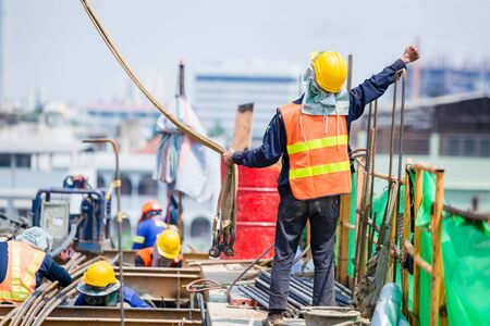 Construction team working at height site. Construction workers raising hands to signal construction crane operators. Builder worker in safety protective equipment.