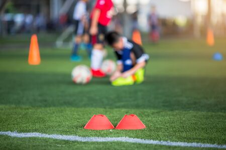selective focus to marker cones are soccer training equipment on green artificial turf with blurry kid players training background. material for training class of football academy. Stock fotó
