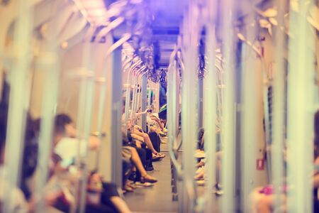 Blurred images of stainless steel poles and many passengers sitting and playing smartphone daily life of the city society in sky train. BTS in Bangkok, Thailand. Blurry people background.