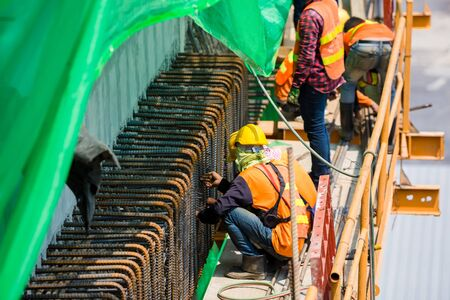 Construction team working at height site. Construction workers fabricating steel reinforcement bar at the construction site. Builder worker in safety protective equipment.