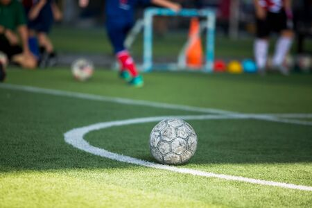 Soccer ball on green artificial turf with blurry soccer team training. Blurry kid player training and soccer equipment in soccer academy. Stock fotó