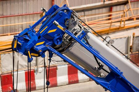 Blue crane boom with hooks and sling cable at construction site. Boom of mobile crane. Stock fotó