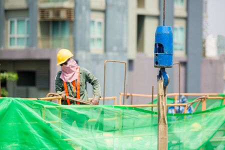 blue hooks and sling cable of mobile crane with blurry worker at construction site.