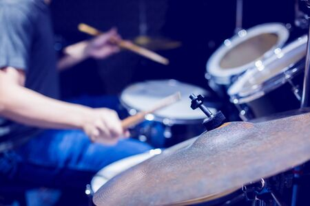 Young musicians wear t-shirts, jeans, and play the drum set and cymbals with wooden drumsticks in music room , the concept of musical instrument. Stock fotó