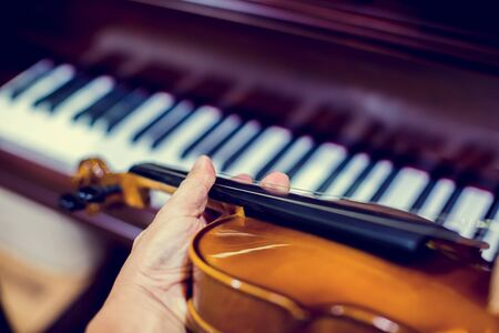 Hand playing the violin with blurry piano in music room or stage. music instrument concept. Stock fotó
