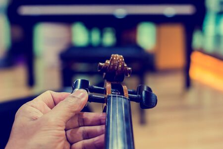 Hand tuning violin with blurry piano in music room or stage. music instrument concept.